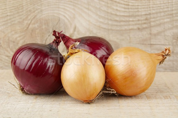 Onions and red onions on wooden background Stock photo © dla4