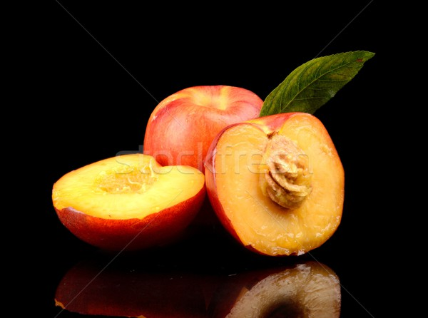 Few sliced nectarines with leaf isolated on black Stock photo © dla4