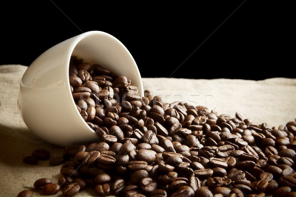 Strewn beans of coffee from a cup on black and flax Stock photo © dla4