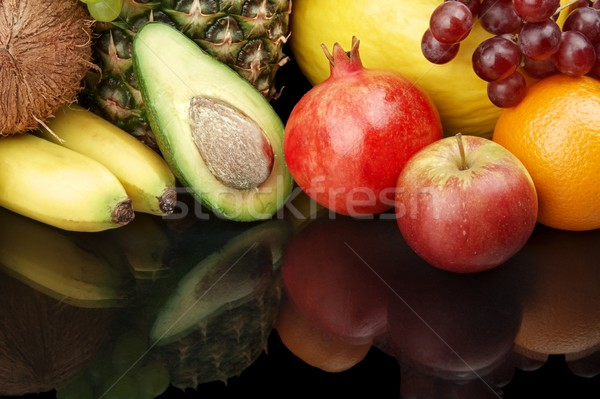 Cropped shot of fruits-grapes,pomegranate,avocado on black with  Stock photo © dla4
