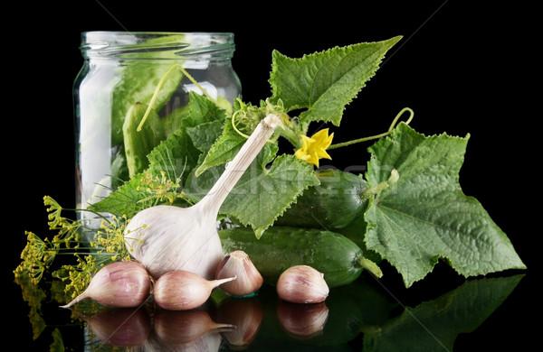 Cucumbers in jar preparate for pickling on black Stock photo © dla4