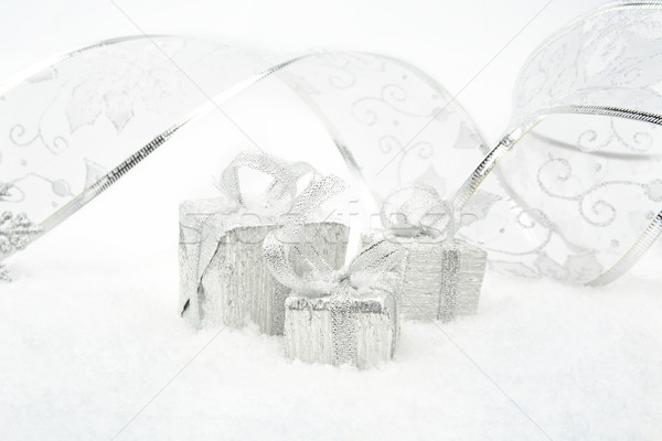 Stock photo: Silver christmas gifts with silver ribbon on snow