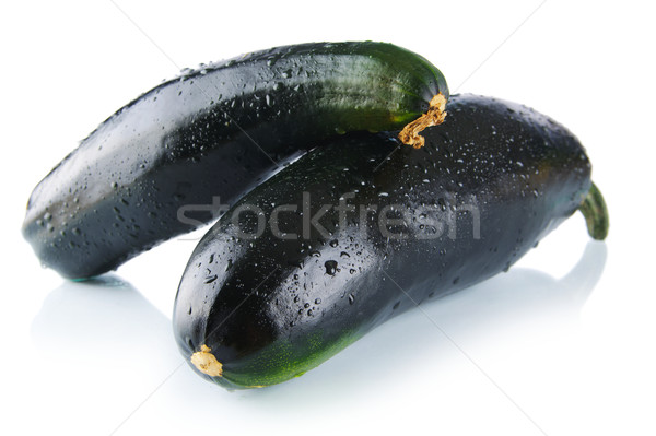 Black wet courgettes on white background Stock photo © dla4