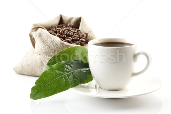 Sack full of coffee beans with green leaves and coffee cup Stock photo © dla4