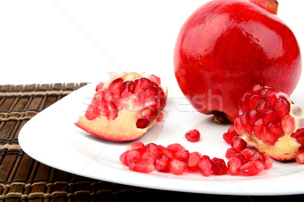 Studio shot open pomegranate on plate wooden mate Stock photo © dla4