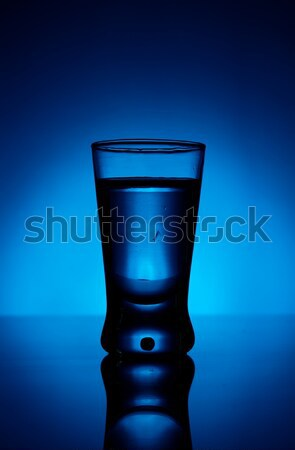 Glass of vodka lit with blue backlight Stock photo © dla4