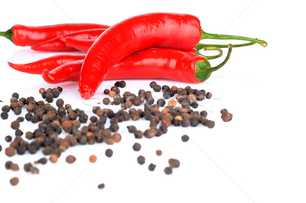 Perspective view of chilli pepper and black pepper on white Stock photo © dla4