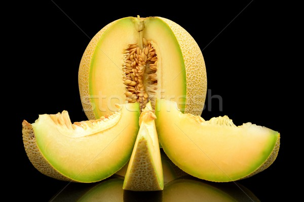 Melon galia notched with slices isolated black in studio Stock photo © dla4