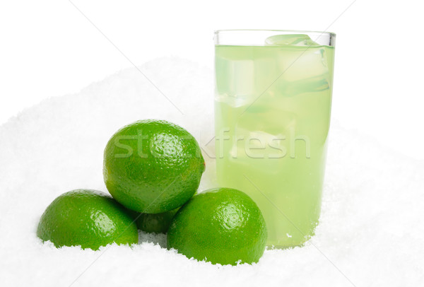 Glass of lime juice with ice cubes,limes on snow on white Stock photo © dla4