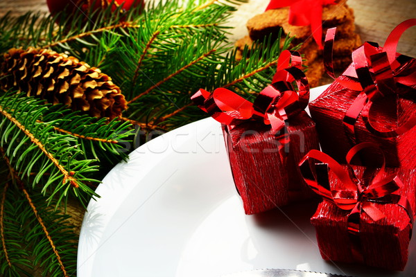 Closeup Christmas plate red gifts pines wooden surface Stock photo © dla4