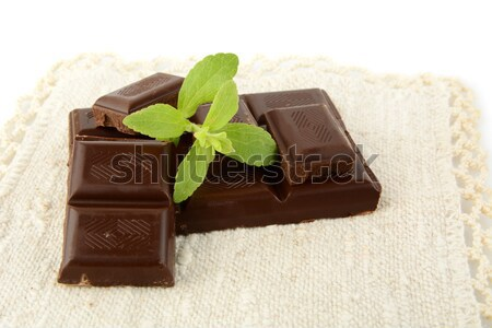 Group of blocks of chocolate with sage on wooden mat Stock photo © dla4