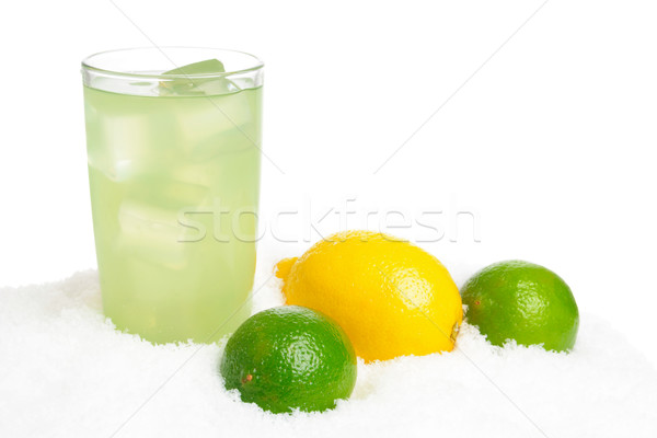 Glass of lime juice with ice cubes,limes,lemon on snow on white Stock photo © dla4