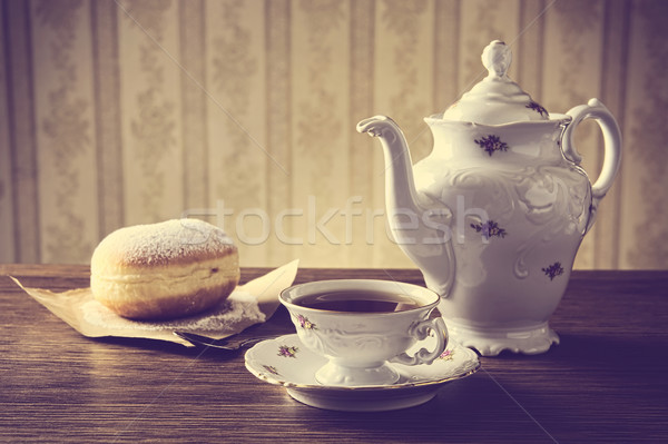 Doughnut with cup of tea on table in old-fashioned   Stock photo © dla4