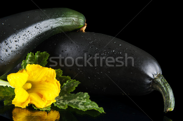 Cropped courgettes with flowers on black background Stock photo © dla4