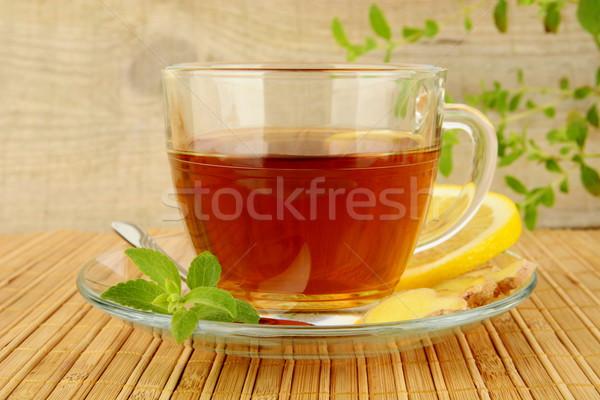 Ginger tea-ingwertee on wooden mat with lemon Stock photo © dla4