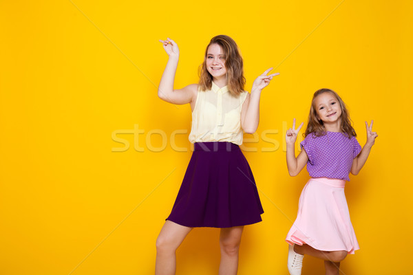 two girls in colored dresses laugh show fingers Stock photo © dmitriisimakov