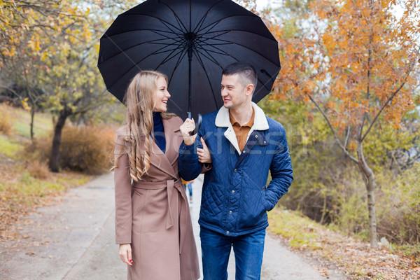 a guy with a girl go under umbrella rain Stock photo © dmitriisimakov