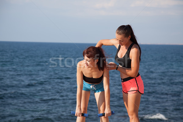 fitness instructor teaches a woman to play sports Stock photo © dmitriisimakov