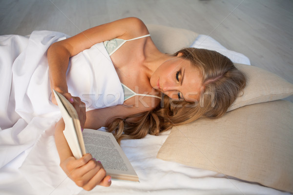 blonde girl reading a book lies in bed Stock photo © dmitriisimakov
