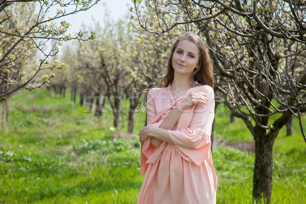 girl in peach dress walks by a blooming garden Stock photo © dmitriisimakov