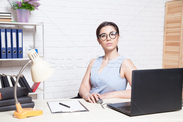 Stock photo: business girl sits in a white Office works at the computer