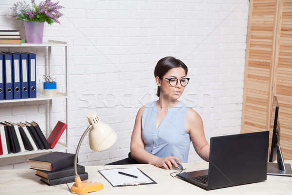 business girl sits in an Office behind a desk with a computer Stock photo © dmitriisimakov