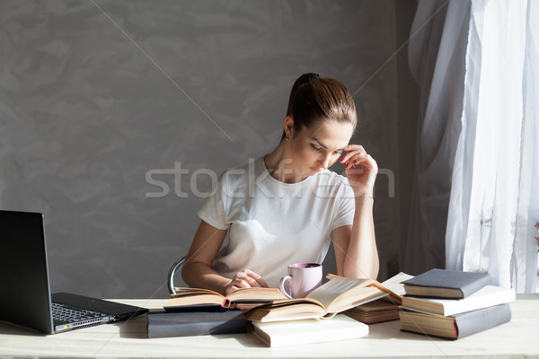 Stock photo: girl works at the computer reads books