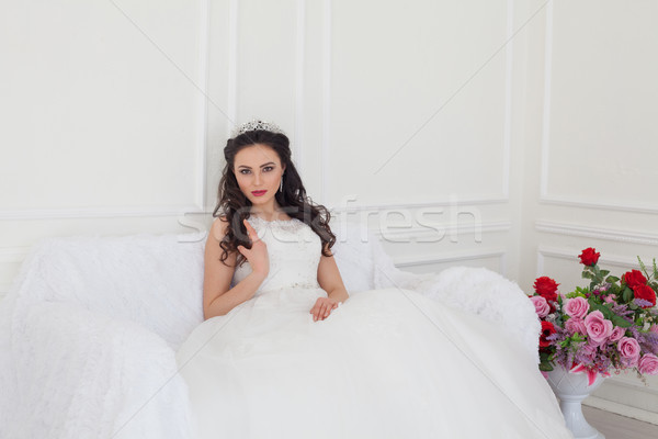 bride in a wedding dress and a crown sits in the white hall Stock photo © dmitriisimakov
