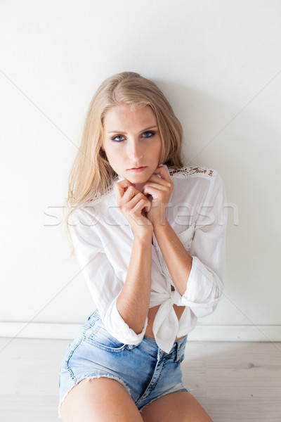 beautiful blonde girl with blue eyes sitting on the floor in a white room 1 Stock photo © dmitriisimakov