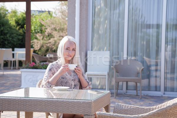blonde girl sitting at the beach restaurant coffee Stock photo © dmitriisimakov
