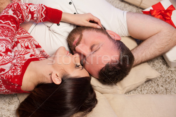 the guy with the girl lying on the floor at the new year Christmas tree Stock photo © dmitriisimakov