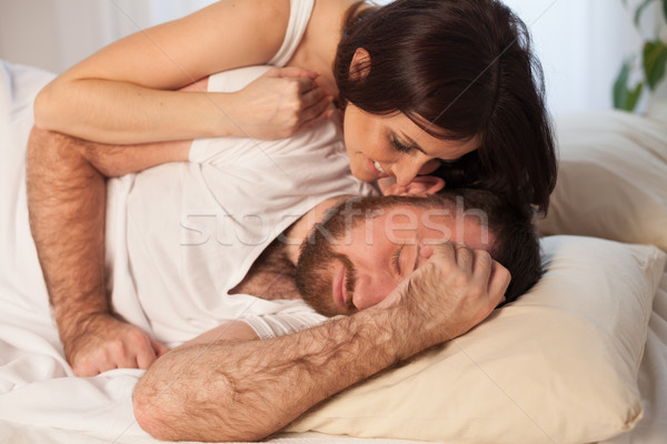 woman gently wakes up in the morning in bed man Stock photo © dmitriisimakov