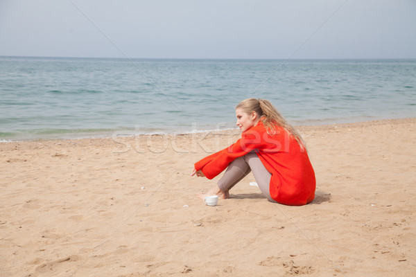 blonde sits on a sandy beach and is looking at the sea Stock photo © dmitriisimakov