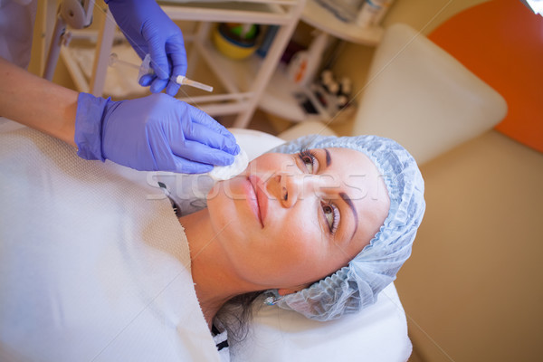 Stock photo: doctor beautician increases lip patient an injection syringe Spa