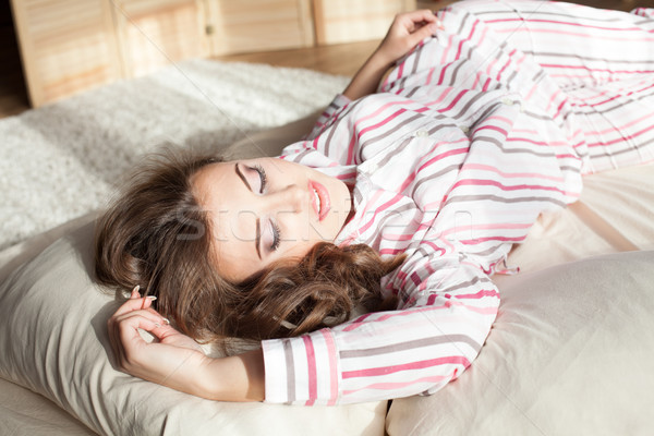 girl in pajamas woke up in the morning is sitting on a bed Stock photo © dmitriisimakov