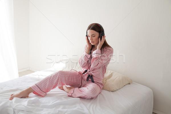 Brunette roze pyjama luisteren naar muziek hoofdtelefoon bed Stockfoto © dmitriisimakov