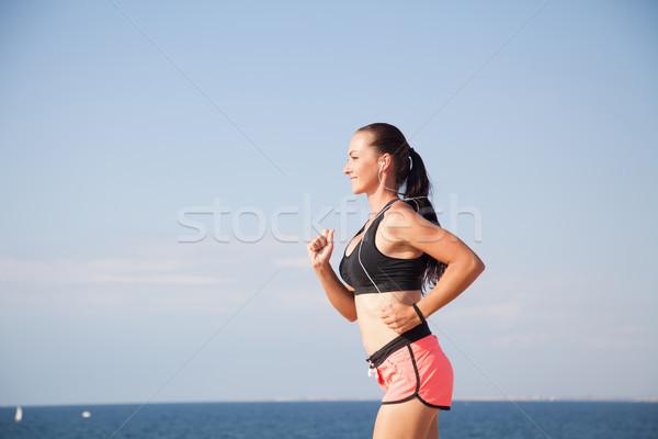 woman on the run sports runs on the beach listening to music Stock photo © dmitriisimakov