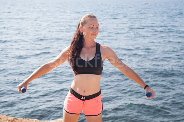 pretty girl plays sports with dumbbells on the beach at the sea Stock photo © dmitriisimakov