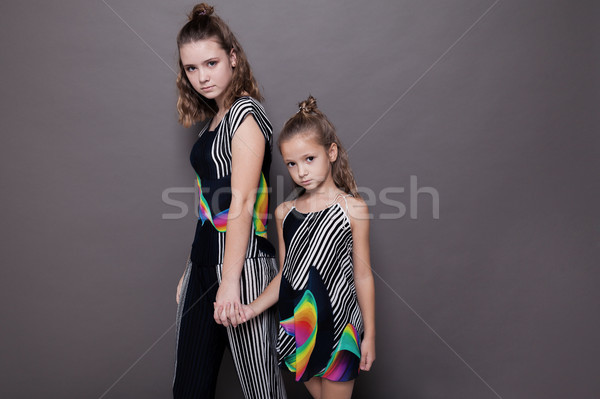 two girls sisters side by side on a grey background Stock photo © dmitriisimakov