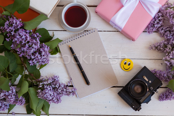 on the white table lilac, notebook, camera Stock photo © dmitriisimakov