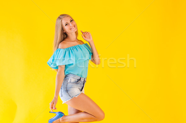 beautiful blonde girl on a yellow background in blue dress Stock photo © dmitriisimakov