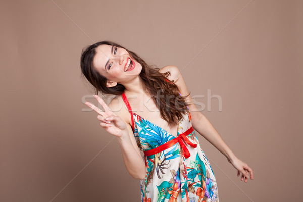 девушки платье два пальцы улыбаясь Сток-фото © dmitriisimakov