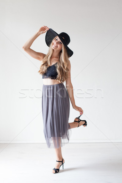 Stock photo: fashionable girl in a hat with a brim poses for advertising