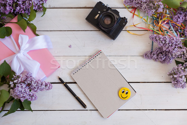 Stock photo: on the white table lilac, notebook, camera, smartphone