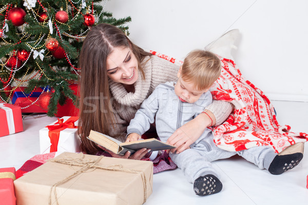 mother reading a book to a child at Christmas new year Stock photo © dmitriisimakov