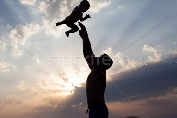 Stock photo: Dad plays with young son silhouette at sunset