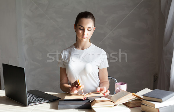 girl is preparing for the exam reading book works at the computer Stock photo © dmitriisimakov