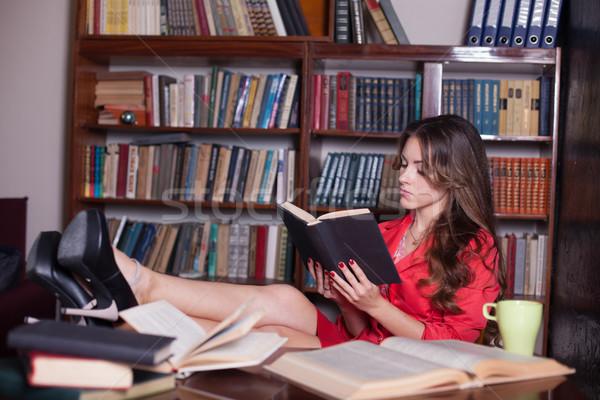 girl reading a book on the table legs Stock photo © dmitriisimakov
