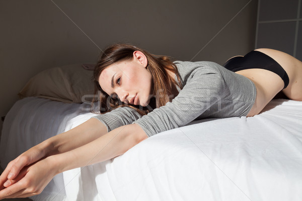 brunette woman after sleeping in bedroom pillows on the bed Stock photo © dmitriisimakov