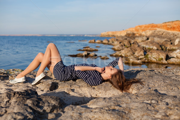 girl lies on her back on a stone Beach Stock photo © dmitriisimakov